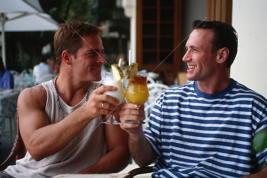 Two men at a cafe having tropical drinks