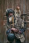 Beggar with monkey, Manali Kulu Valley. Himachal Pradesh, India. Vertical format.
