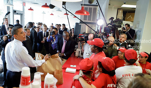"Washington, DC - May 29, 2009 -- United States President Barack Obama grabs his take-away lunch bags at a ""Five Guys"" burgers and fries restaurant, Friday, May 29, 2009 in Washington, DC.  President Obama traveled with his motorcade to the burger restaurant in Southeast Washington. .Credit: Brendan Smialowski - Pool via CNP"