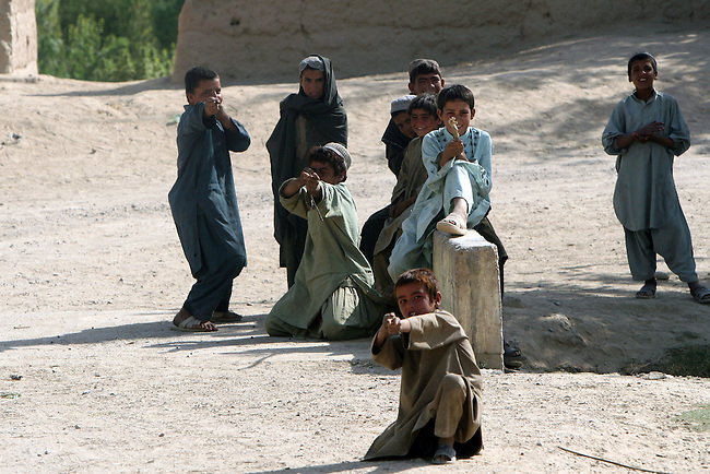 Afghan boys pretend to shoot at Canadian soldiers after they leave a village in Zhari district in Kandahar province, Afghanistan. Canadian soldiers fight daily skirmishes for control of Zhari, where the hardline Taliban movement originated in the early 1990s. Sept. 27, 2008. DREW BROWN/STARS AND STRIPES
