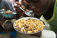 Rwanda. Southern province. District of Muhanga. Central jail of Gitarama. Once a day at 4 pm, the minors in detention receive food. A group of black teenagers eats a plate of beans and corns. Minors block. Detention pending trial and after trial, when sentenced to prison. The non-governmental organization (NGO) Fondation DiDé - Dignité en détention runs the Encademi (Encadrement des mineurs) program. Prison centrale de Gitarama. Quartier des mineurs.  © 2007 Didier Ruef
