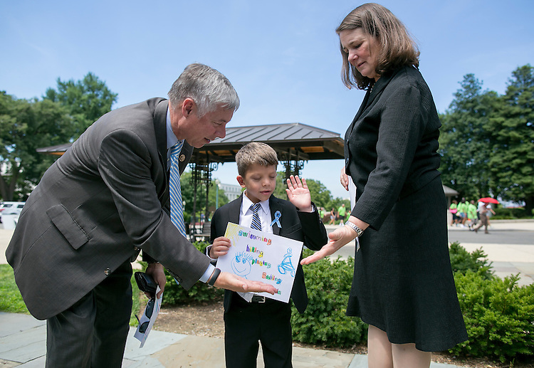 UNITED STATES - JUNE 10 - Rep. Fred Upton, R-Mich., left, and Rep. Diana DeGette, D-Colo., high five Max Schill, 6, from Williamstown, N.J., after the U.S. House of Representatives voted in favor of the 21st Century Cures Act on Capitol Hill in Washington, Friday, July 10, 2015. Upton and DeGette spearheaded the act. (Photo By Al Drago/CQ Roll Call)