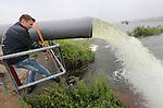 Foto: VidiPhoto<br /> <br /> DODEWAARD - Pompen of verzuipen maandag. Een achttal akkerbouwers en veehouders met grond in de uiterwaarden tussen Dodewaard en Ochten heeft de handen ineengeslagen om te voorkomen dat hun gewassen helemaal verloren gaan. Door het aanhoudende hoge rivierwater stijgt het kwelwater in de polder en dreigt het 400 ha. grote gebied (inclusief grasland en natuurgebied) onder water te komen. 's Winters is dat geen probleem, maar in deze tijd staat er zo'n 200 ha. aan gewassen als voeder- en suikerbieten, ma&iuml;s en bonen. Zonder de inzet van een enorme installatie die 4000 kubieke meter water per uur uit de polder pompt, gaat deze wintervoorraad voor het vee verloren. De schade bedraagt nu al tussen de 50.000 en 100.000 euro. Bij de grootste gebruiker van het gebied, loonbedrijf Van der Woerd uit Zoelen, staat al zo'n 5 ha. ma&iuml;s en bieten onder water. Bij melkveehouder Van Rooijen uit Dodewaard eenzelfde gebied aan ma&iuml;s. Bij de andere agrari&euml;rs is dat minder, maar in totaal staat er zo'n 25 ha. aan gewassen blank. Het water in de Waal staat al drie weken boven de 12 meter. Zo'n lange periode met hoogwater in deze tijd van het jaar is nog niet eerder voorgekomen. Het hoge water in de grote rivieren houdt nog zeker tot eind deze week aan.