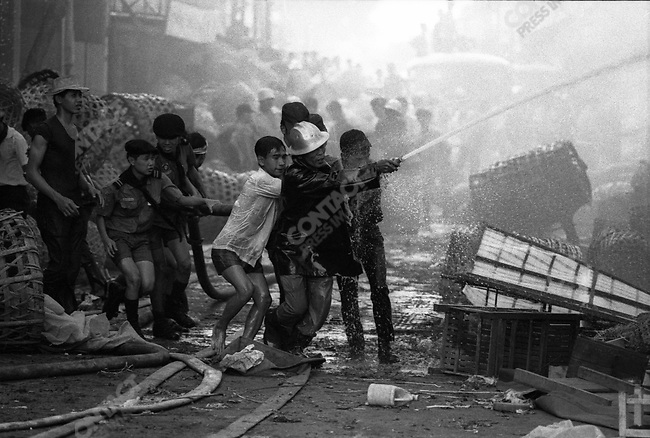 Firefighters and civilians fight a fire that broke out in a public market, Saigon, South Vietnam, January 1971