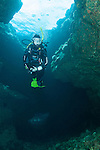 Kona, Big Island of Hawaii, Hawaii; a scuba diver swimming in a lava tube with sunlight coming in from above