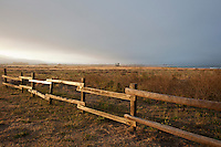 Day breaks at the trailhead of the South Whitehouse Creek Trail where a wooden fence marks the boundry to California's Ano Nuevo State Reserve.