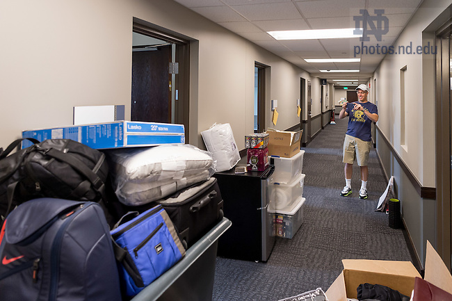 "August 19, 2016; Jerry Quinn '89 takes a photo of the supplies his son Patrick brought to his Dunne Hall dorm room for move-in day of Welcome Weekend 2016. A former Morrissey Manor resident, Jerry was impressed with Notre Dame's newest men's residence hall. ""This isn't a dorm, it's a hotel,"" he said. (Photo by Matt Cashore/University of Notre Dame)"