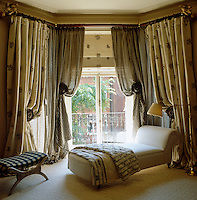 Wooden finials hold open floral curtains and the sheer gingham under-curtains which dress this bay window