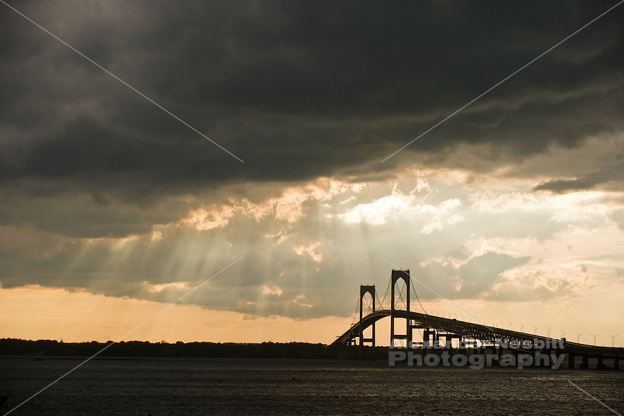 USA, Newport, RI - Rays of light breakthrough dense storm clouds as they pass over the Newport Pell Bridge and Narragansett Bay.