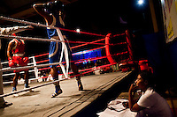 Razia Shabnam judges a bout at an all-India invitational boxing competition in the neighbouring town of Burnpur, Calcutta, West Bengal, India. Razia Shabnam, 28, was one of the first women boxers in Kolkata. She was also the first woman in her community to go to college. She is now a coach and one of only three international female boxing referees in India. Photo by Suzanne Lee for Panos London