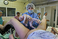 Alyona Kozlova, 23, gives birth at the Moscow Planning Center and Reproduction Maternity Home. Doctors are Zinaida Rerinova and Arinato Vmosyan and the midwife is Yuliya Katlinskaya. The maternity home delivers about 8000 children a year... about 20 a day or so... This is the most of any maternity hospital in Russia.  There are 117,000 delivered in 2009 in all of Moscow.  1,800,000 were born in Russia in 2009 which is 27,000 more than the deaths that year.  So Russia is basically at the replacement rate, but there are not as many breeders in the lineup moving forward... so the state has instituted a number of policies including free housing for immigrants and a one time payment of over $10,000 for a woman to have either the 2nd, 3rd or 4th baby.