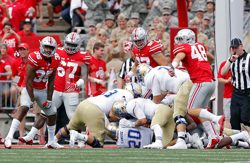 Ohio State Buckeyes linebacker Chris Worley (35) celebrates after Ohio State Buckeyes safety Malik Hooker (24) and Ohio State Buckeyes cornerback Gareon Conley (8) stop Tulsa Golden Hurricane running back James Flanders (20) on 4th down on the 1 yard line in the 1st quarter of their game at Ohio Stadium in Columbus, Ohio on September 10, 2016.  (Kyle Robertson / The Columbus Dispatch)