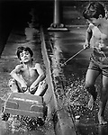 Leopold Dominguez, 10, holds on for dear life as his brother Eloy, 8, pulls him along through a water-filled storm gutter on Miami Beach, 1979.