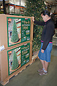 Mid adult woman shopping for an artificial Christmas tree with lights. California, USA