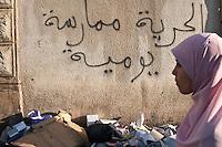 Tunisia, Tunisi, il dopo rivoluzione. Profilo di una ragazza velata in una strada  con spazzatura per terra e un muro con delle scritte in arabo.<br /> TUNISIA after spring revolution  femme voil&eacute;e