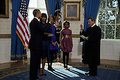 President Barack Obama is officially sworn-in by Chief Justice John Roberts in the Blue Room of the White House during the 57th Presidential Inauguration in Washington, Sunday, Jan. 20, 2013. Next to Obama are (L-R) First Lady Michelle Obama, holding the family bible, and daughters Malia and Sasha. (AP Photo/Pool, Charles Dharapak).Credit: Charles Dharapak / Pool via CNP