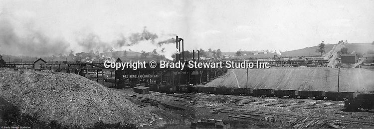 Export PA:   View of the Westmoreland Coal Company, Export Mine tipple, with the town of Export in the background and the Turtle Creek Branch of the Pennsylvania Railroad in the foreground. This view of the mine was created with two 8x10 prints put together  to give the appearance of a panorama view.  The coal is being loaded into PA Railroad hopper cars on the Turtle Creek branch line.