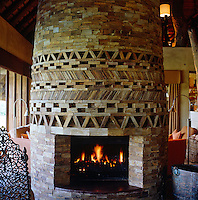 The stone-clad fireplace is located in the centre of the living room and divides it into two sitting areas