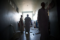 August 11, 2012 - Azaz, Aleppo, Syria: A group of men stand by in a corredor of an improvised refugee center in Azaz, where 32 families who fled the combat areas are temporarily living. (Paulo Nunes dos Santos/Polaris)