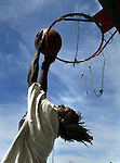Yahya Abdul-Mateen (17) reaches for a basket hoop  at McClymonds High School in West Oakland, California.