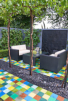 Colorful mixed tile patio and walls creating an outdoor living room with sofas furniture, coffee table, climbing vine decor, shade under trees, sense of enclosure outdoors in backyard for upscale landscaping and gracious living