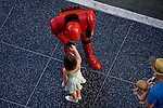 A young girl is greeted by a man dressed in a super hero costume on Hollywood Blvd.