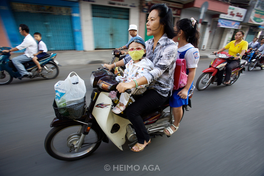 Cholon (Chinatown). Motorcycles during morning rushhour. Child protected from polluted air and dust with a facial mask.