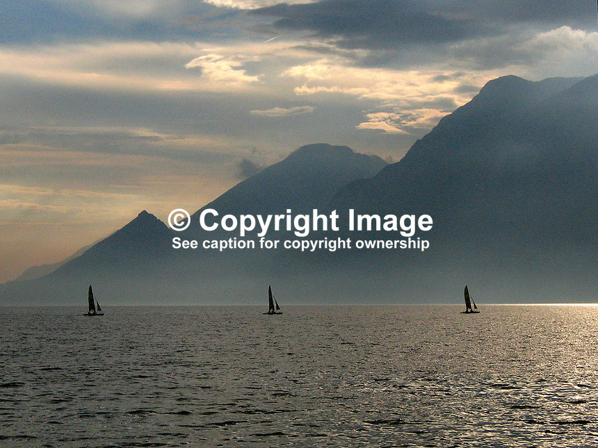 Three yachts on Lake Garda, Italy, at dusk, 200609180142..Copyright Image from Victor Patterson, 54 Dorchester Park, Belfast, UK, BT9 6RJ..Tel: +44 28 9066 1296.Mob: +44 7802 353836.Voicemail +44 20 8816 7153.Skype: victorpattersonbelfast.Email: victorpatterson@mac.com.Email: victorpatterson@ireland.com (back-up)..IMPORTANT: If you wish to use this image or any other of my images please go to www.victorpatterson.com and click on the Terms & Conditions. Then contact me by email or phone with the reference number(s) of the image(s) concerned.