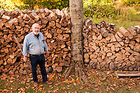 Bud Chamberlin with firewood at Chamberlin's Ole Forest Inn on Big Manistique Lake near Curtis Michigan in autumn.