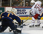 12/11/04  Omaha, NE University of Nebraska at Omaha 's Bryan Marshall fires a shot at  Lake Superior State goalie Jeff Jakaitis. (photo by Chris Machian/for Prarie Pixel Group)