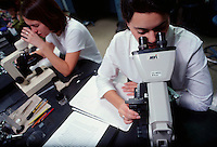 Two college students using microscopes in science lab