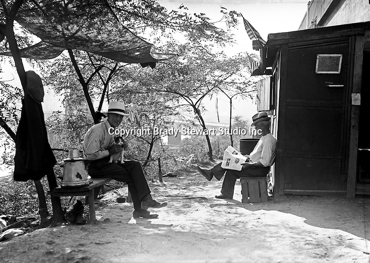 Pittsburgh PA: Two men and a cat passing the time - the Strip District of Pittsburgh 1930.  During the depression, the area from the PA RR Station to the 17th street bridge was called Shantytown.  Father Cox, a local priest, helped the residents through food kitchens and highlighting their plight.  Brady Stewart photographed the area for the City of Pittsburgh.