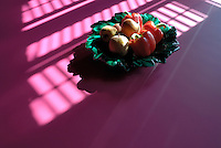 A bowl of apples and red peppers on the fuschia pink surface of the dining table