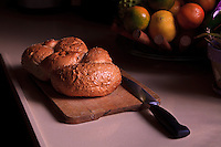 A loaf of challah bread on a cutting board with a bowl of fruit in the background.