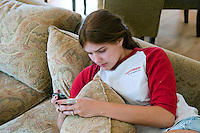 Teenage Girl Texting laying on Sofa
