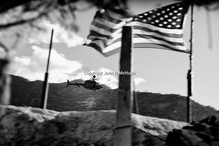 A Kiowa helicopter flies past Checkpoint 2.5, beside Saw village, in Kunar province, 01 Dec 2011. (John D McHugh)