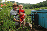 Ionel Farcas Cozmin, 54 years old, from Mures in Transylvania, with his grandson Catalin observes a hive on a scale and thus determines the nectar harvest for the day. When the quantity of nectar is no longer sufficient, it's time to break camp.