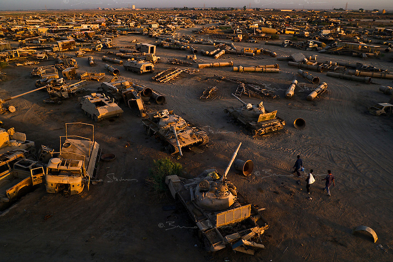 Baghdad, Iraq, June 12, 2003.Three young Baghdadis arrive at dawn to work before the Iraqi summer heat to recuperate metals, wheels, rubber, electric wiring and...explosives in a gigantic cemetery for disabled Iraqi military equipment just outside Baghdad. Thousands of Saddam's  toys -tanks, trucks, apc's, field guns, missile containers and military equipment of all sorts- litter the plain as far as the eye can see....