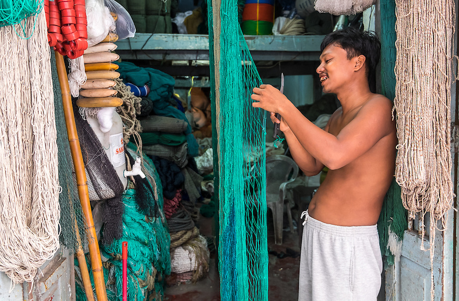 YANGON, MYANMAR - CIRCA DECEMBER 2013: Merchant in the streets of Yangon webbing a fishing net in his storefront.