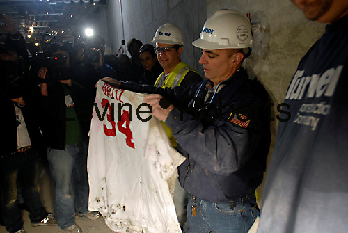 Construction workers Frank Gramarossa, center, and Sal Carrini, left, display a Boston Red Sox jersey bearing the name of the player David Ortiz, number 34 which was buried in the concrete of the new Yankee Stadium in the Bronx  borough of New York on April 13, 2008. A construction worker, who is a Boston Red sox fan, buried the jersey in the concrete in a lower level of the stadium hoping to put a curse on the Yankees who have a long-time rivalry with the Boston team. (© Richard B. Levine)