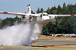 Calfire Grumman S2-T Turbo Tracker based in Grass Valley, California, drops a load of water the length of the runway during a demonstration at the Nevada County Airport. The Turbo Tracker is a civilian conversion of the Navy's S-2 Tracker. The Calfire fleet, formerly California Department of Forestry, includes 23 of the Turbo Trackers located throughout the state. Each aircraft is capable of carrying 1200 gallons of water or retardant and able to reach a fire within 20 minutes.