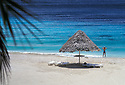 Thatched beach shelter, lounge chairs, and woman putting on snorkeling gear;  Sunset Waters Beach Resort, Curacao, Netherlands Antilles..