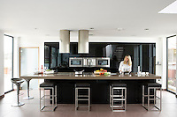 Lisa Manifold photographed at the long Quartz stone floating island in the kitchen/living area of her contemporary open-plan house in Nottingham
