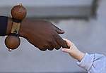 A white - caucasion young male child holds hands with a black - african amrican male on February 11, 2003 in FL.