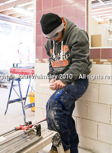 Tiling student tidying up the edge of a freshly cut tile, Able Skills, Dartford, Kent.
