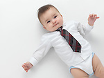 Little baby boy wearing a dress shirt and a neck tie isolated on white background