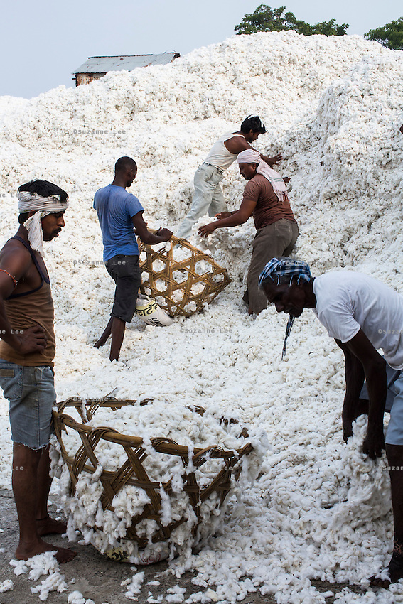 Workers move basket-loads of cotton on their heads at a ginning factory contracted by Pratibha, a Fairtrade-certified establishment, in Maheshwar, Khargone, Madhya Pradesh, India on 13 November 2014. Photo by Suzanne Lee for Fairtrade