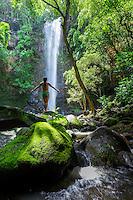 A woman soaks in the sun and spray at Uluwehi Falls, Kaua'i.