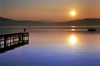 An idyllic sunset scene at Viverone lake in Piedmont, Italy. The heron on the jetty was really a nice model, he posed for an entire session while the sun was slowly setting.
