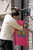 Man cleans sign for Shanghai Tang designer clothes shop, owned by David Tang, Xintiandi, China